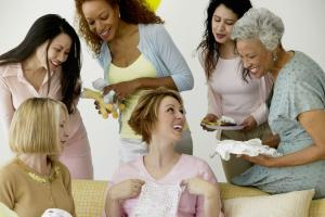 Group of women admiring gifts at baby shower, smiling