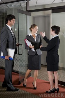 man-holding-door-for-talking-business-woman
